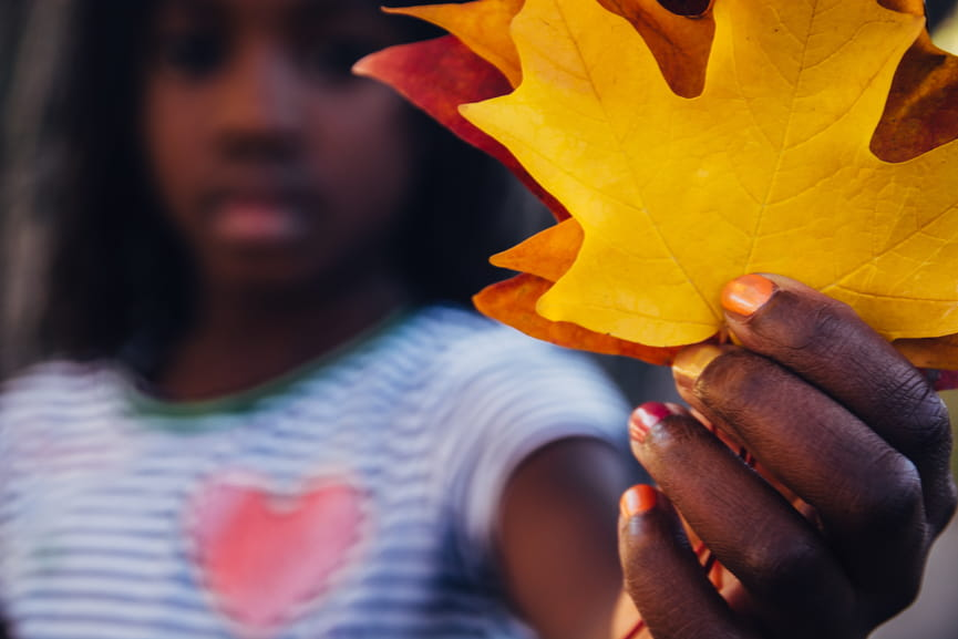 Young girl holding close up of leaves