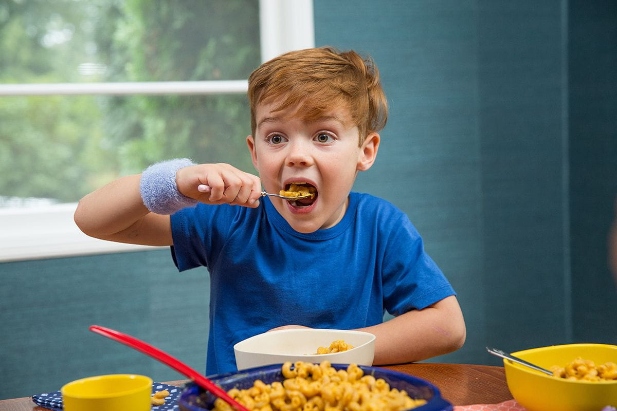 boy taking bite of mac and cheese