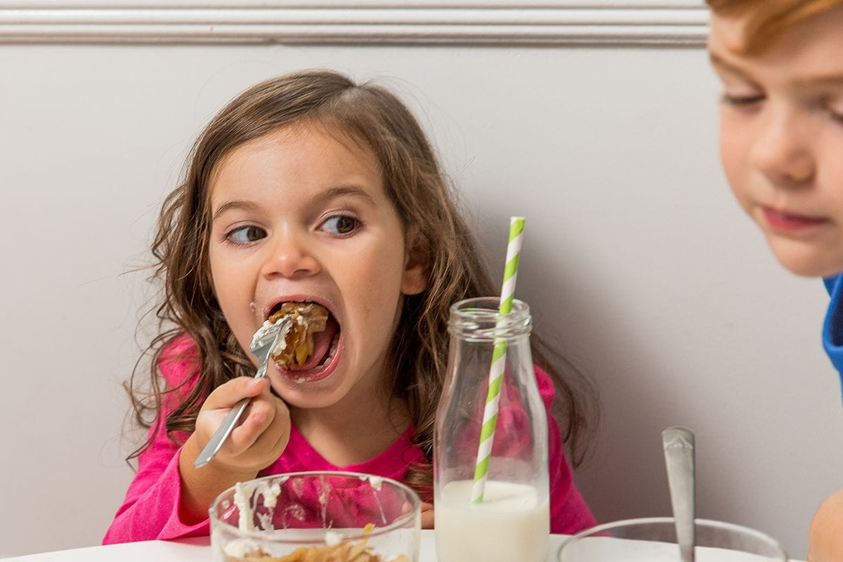 girl biting into apple crisp on fork milk bottle