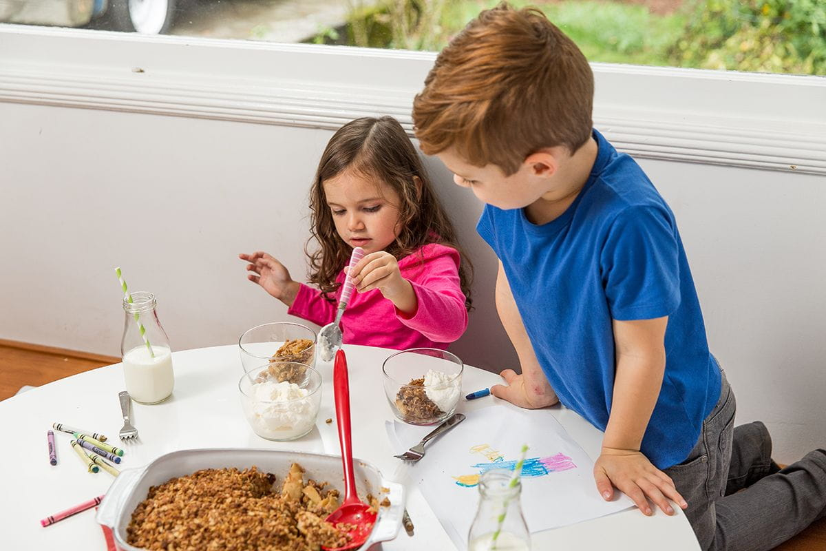 boy and girl at table apple crisp and whipped cream