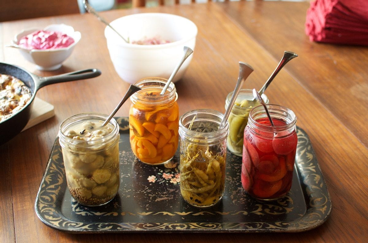 pickled produce in jars on a tray