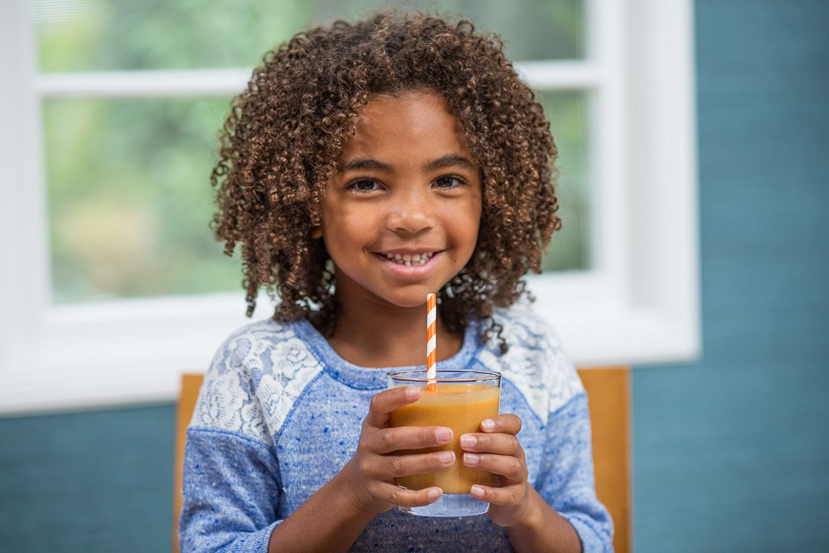 smiling girl with smoothie and a straw