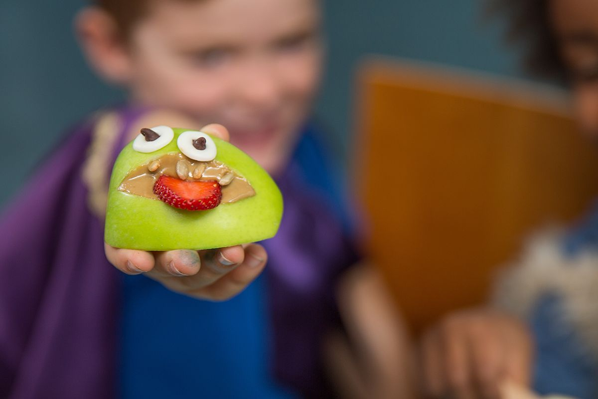 child holding up monster apple mouth
