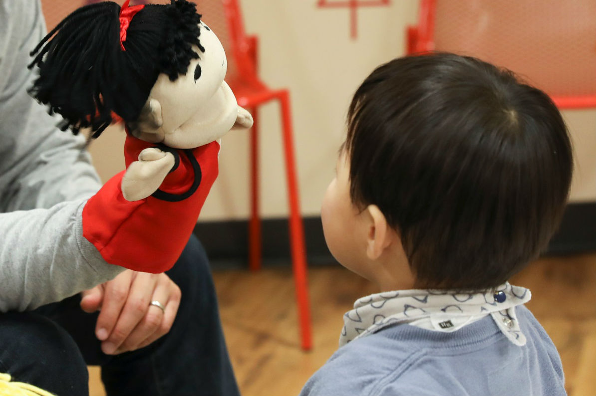 boy looking at puppet