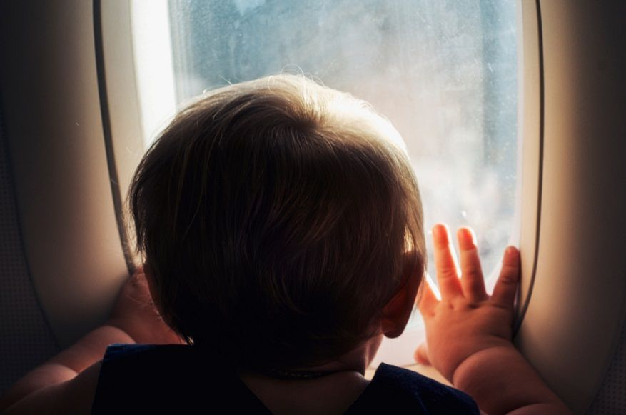 boy looking out airplane window