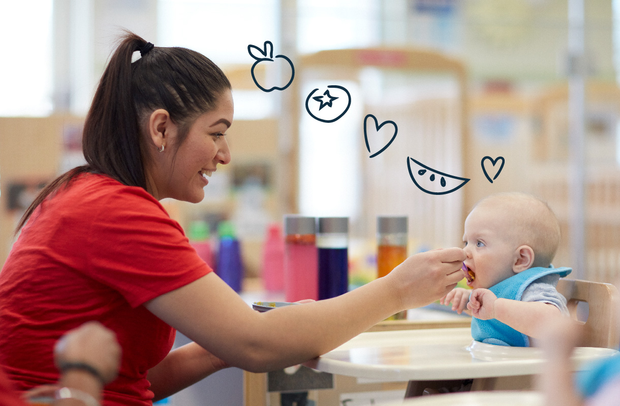 teacher spoon feeding infant